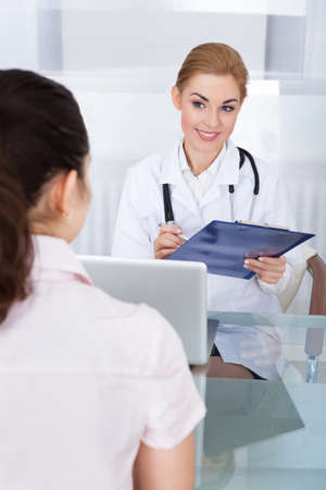 health check: Happy Smiling Doctor Talking With Patient Holding Clipboard At Clinic Stock Photo