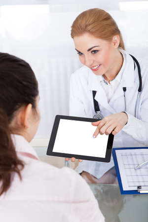 Portrait Of Young Female Doctor Showing Digital Tablet To Patient At Clinic photo
