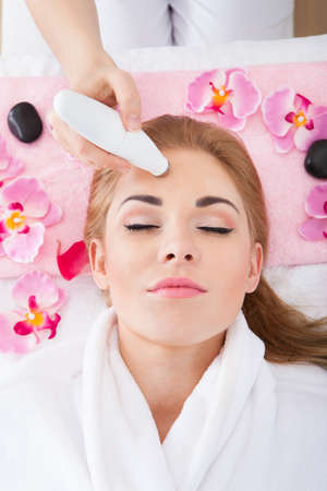 High Angle View Of Woman Getting Microdermabrasion Therapy In Spa Stock Photo
