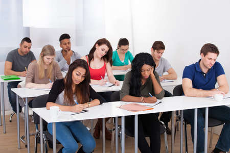 Group of multiethnic college students writing at desk in classroom photo