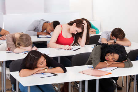classmate: Bored female college student with classmates sleeping at desk in classroom Stock Photo