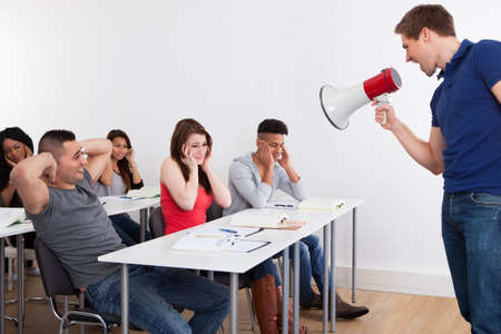 frustrated student: Angry teacher shouting through megaphone on university students in classroom