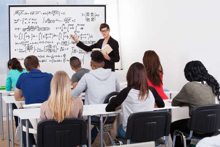 college professor: Young teacher teaching math formulas to college students in classroom Stock Photo