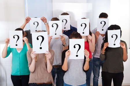 Group multiethnic university students holding question mark signs in front of their faces photo