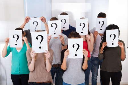 confundido: Grupo multi�tnico estudiantes universitarios con carteles en el signo de interrogaci�n delante de sus caras