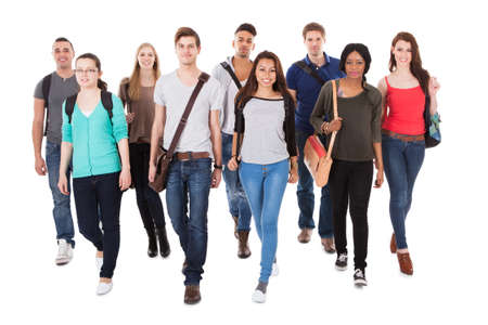 from the front: Full length portrait of confident university students walking over white background