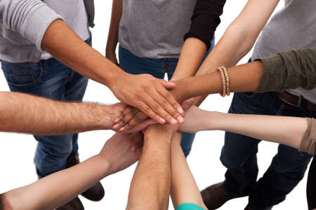 diverse hands: High angle view of multiethnic college students stacking hands against white background Stock Photo
