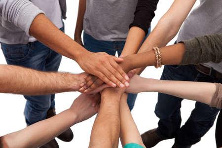 trabajo en equipo: Vista de ángulo alto de los estudiantes universitarios multiétnicas apilamiento manos contra el fondo blanco Foto de archivo