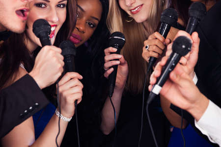 Portrait of happy multiethnic friends singing into microphones at karaoke party Stock Photo