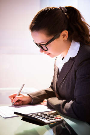 financial audit: Young businesswoman calculating tax at desk in office
