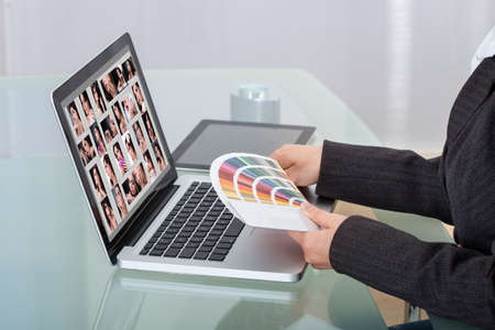 retouch: Cropped image of photo editor with color swatches working on laptop at desk