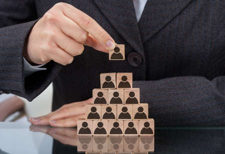 Midsection of businesswoman stacking wooden team blocks at table Stock Photo
