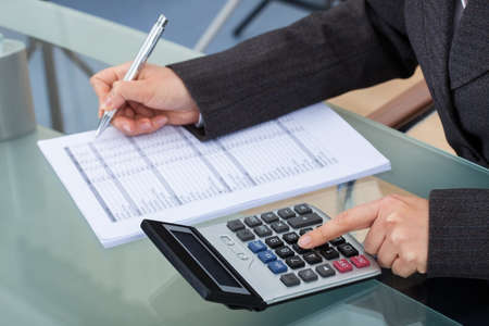Midsection of businesswoman calculating tax at desk in office photo