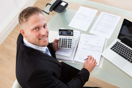 feasibility: View from above of a friendly businessman at work in the office looking up from his desk at the camera with a smile Stock Photo