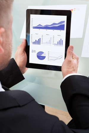 over the shoulder view: Businessman looking at a series of graphs on his tablet computer as he works at his desk  over the shoulder view of the screen