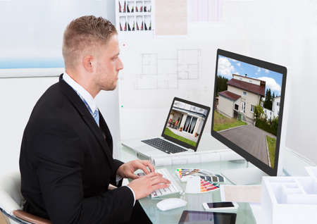 architect office: Businessman or estate agent checking a property portfolio online while sitting at his desk in the office looking at the exterior of a rural house visible on the desktop monitor