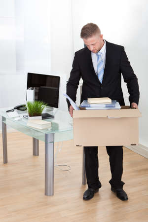 laidoff: Dejected businessman made redundant or fired carrying a cardboard box full of his personal belongings with his head low as he leaves his office