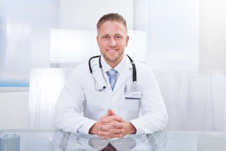 looking around: Smiling doctor or consultant sitting at a desk with his stethoscope around his neck looking at the camera