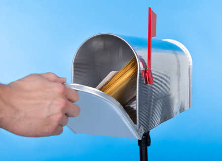 direct mail: Man opening his mailbox to remove mail inside  close up of his hand on the open door against a blue sky