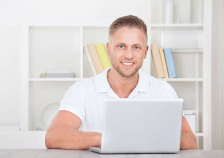 short sleeved: Smiling young man in a short sleeved shirt sitting working at home on a laptop in a home office