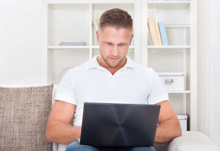 man using computer: Attractive young man sitting in his living room on the sofa using a laptop computer balanced on his knee to surf the internet