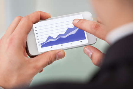 Cropped image of businessman analyzing graph on smart phone in office photo