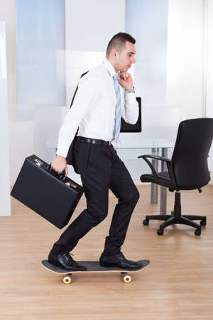 Full length side view of young businessman on skateboard in office photo