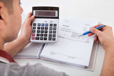 home expenses: Cropped image of young man calculating financial expenses at home Stock Photo