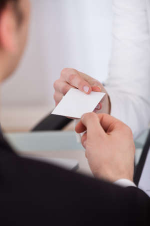 Close-up of businessman giving visiting card to female colleague at desk in office photo