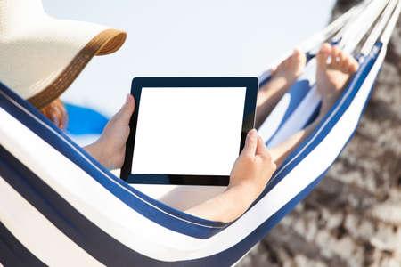 Žena pomocí digitálního tabletu a zároveň relaxaci v houpací síti na pláži