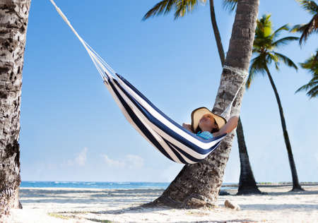 palmtree: Woman relaxing in hammock at the beach