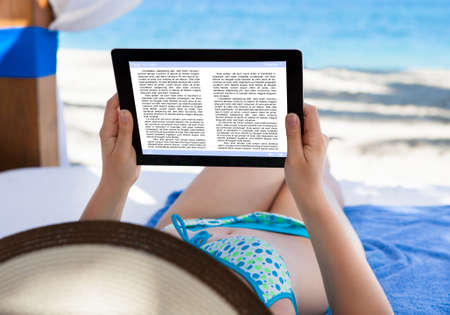 Woman reading e-book in gazebo at beach photo