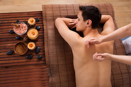 acupressure: High angle view of young man receiving back massage in spa