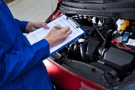 mantenimiento: Sección media de celebración portapapeles mecánico en frente del motor de un coche abierto en la calle