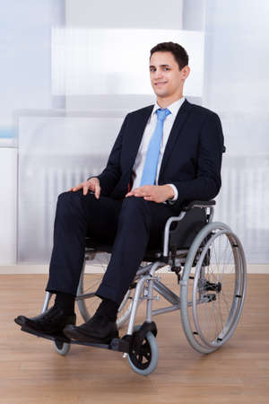 wheelchair access: Portrait of confident disabled businessman sitting on wheelchair in office Stock Photo