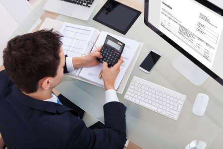 ハイアングルの実業家のオフィスの机で税金を計算します。