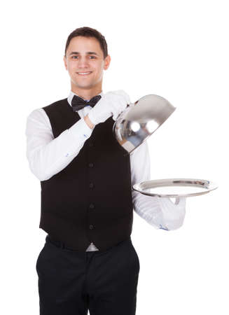 cloche: Portrait of confident waiter holding metal cloche lid cover over empty tray over white background