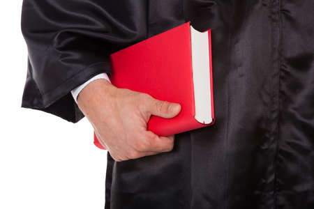 red book: Midsection of male judge holding statute book against white background