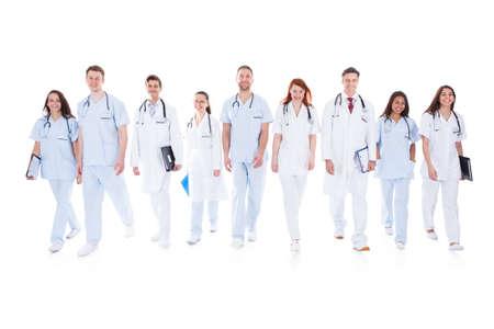 Grote diverse groep van artsen en verpleegkundigen in uniform lopen naar camera geïsoleerd op wit