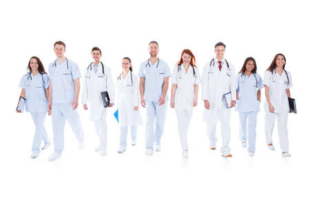doc: Large diverse group of doctors and nurses in uniform walking towards camera isolated on white
