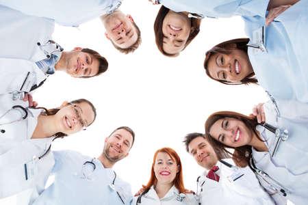 Đội ngũ y tế đa sắc tộc đa dạng lớn đang đứng nhóm lại trong một vòng tròn tất cả nhìn xuống các camera và mỉm cười cô lập trên nền trắng với copyspace trung ương
