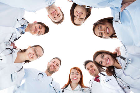 Large diverse multiethnic medical team standing grouped in a circle all looking down at the camera and smiling isolated on white with central copyspace