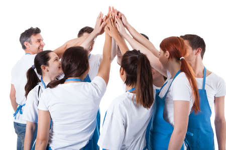 Group of cleaners making high five gesture. Isolated on white photo