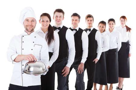 Velká skupina číšníky a servírky stojí v řadě. Samostatný na bílé