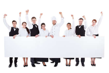 hotel staff: Cheerful excited catering staff showing banner. Isolated on white Stock Photo