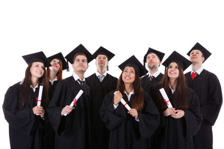 Happy smiling group of multiethnic graduates dressed in black academic gowns and mortarboard hats standing grouped close together with their certificates  isolated on white photo