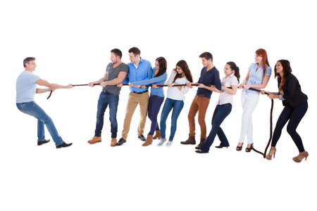 Group of people having a tug of war against one man as they pull on opposite sides of the rope conceptual of leadership  individuality  determination and challenge  on white photo