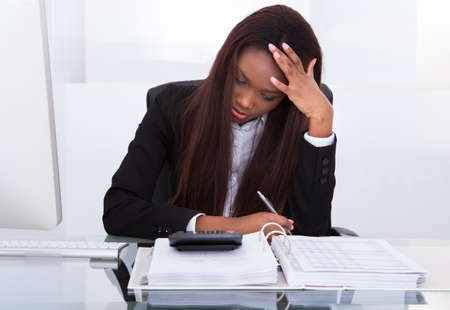 Gespannen jonge zakenvrouw berekenen van de belasting op het bureau in het kantoor