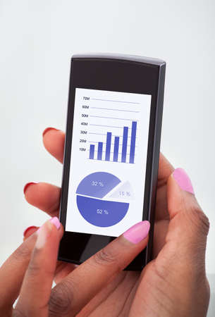 Cropped image of businesswoman analyzing financial charts on mobilephone in office photo