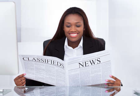 reading news: Happy businesswoman reading newspaper at desk in office
